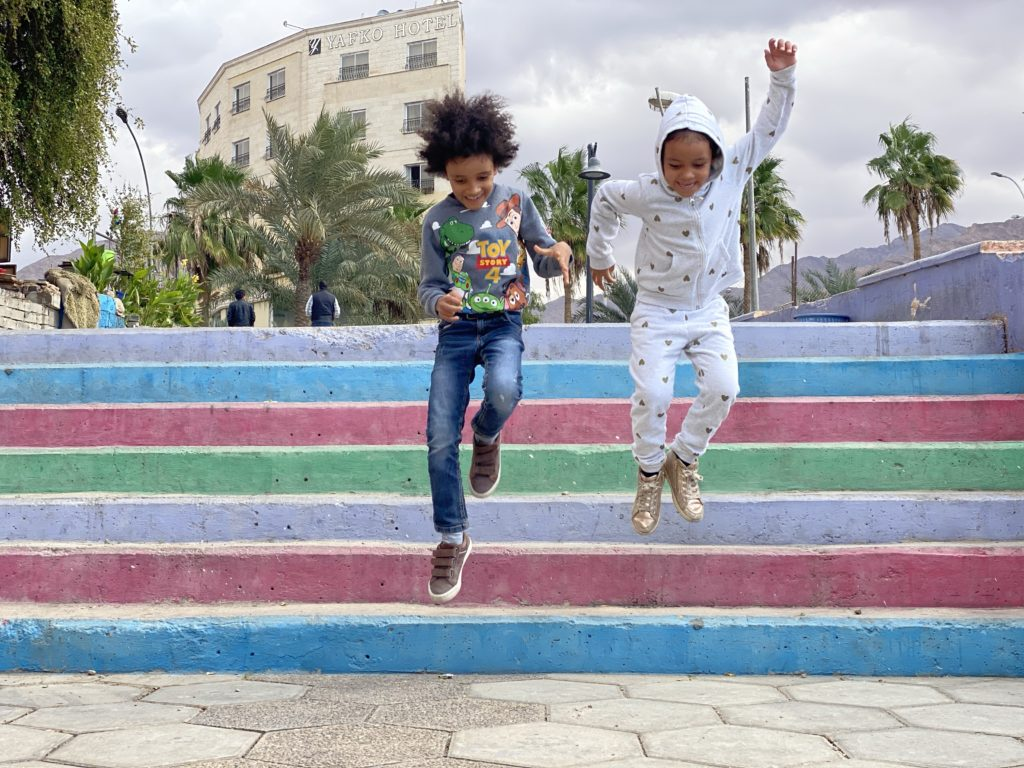 my children jumping on a colourful steps in Aqaba's castle
