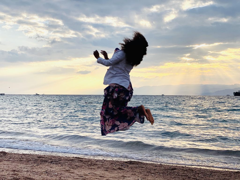 woman jumping in Aqaba red see beach, sunset